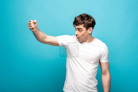 Photo for Angry young man looking away and showing fist on blue background - Royalty Free Image