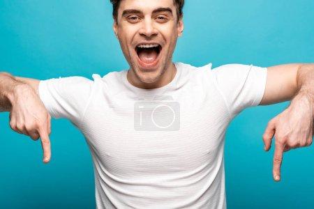 Photo pour Jeune homme gai pointant vers le bas avec des doigts et souriant à l'appareil-photo sur le fond bleu - image libre de droit