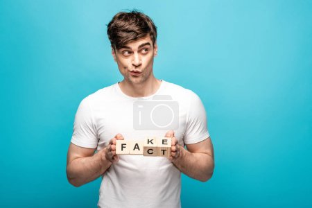 Photo for Discouraged young man holding wooden cubes with fake fact lettering on blue background - Royalty Free Image