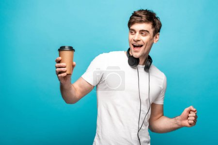 Photo for Cheerful man with headphones looking away while holding paper cup on blue background - Royalty Free Image