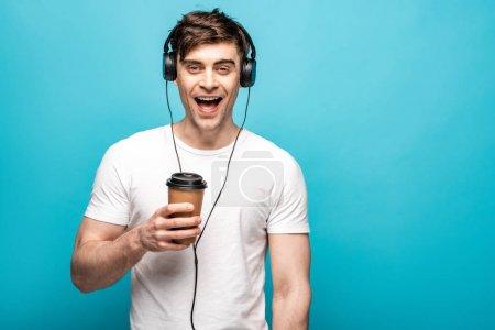 Photo pour Jeune homme heureux écoutant la musique dans des écouteurs tout en retenant la tasse jetable sur le fond bleu - image libre de droit