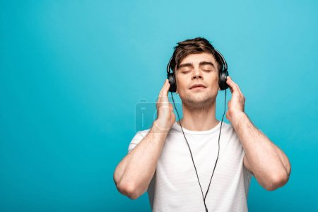 Photo for Dreamy young man in headphones listening music with closed eyes on blue background - Royalty Free Image