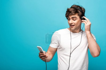 Photo for Handsome man listening music in headphones and using smartphone on blue background - Royalty Free Image