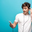 Handsome man listening music in headphones and using smartphone on blue background