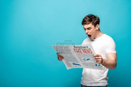 Photo for Angry young man reading newspaper with fake news on blue background - Royalty Free Image