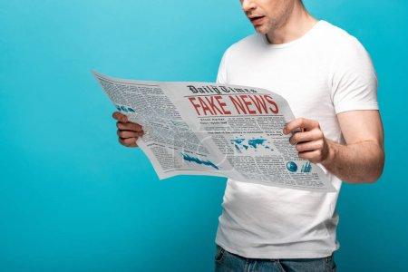 Foto de Cropped view of man reading newspaper with fake news on blue background - Imagen libre de derechos