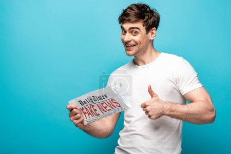 Photo pour Homme joyeux montrant pouce vers le haut tout en tenant journal avec de fausses nouvelles sur fond bleu - image libre de droit