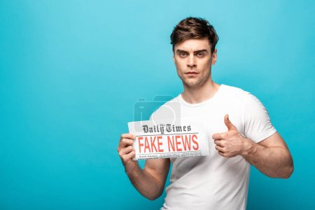 Foto de Serious young man showing thumb while holding newspaper with fake news and looking at camera on blue background - Imagen libre de derechos