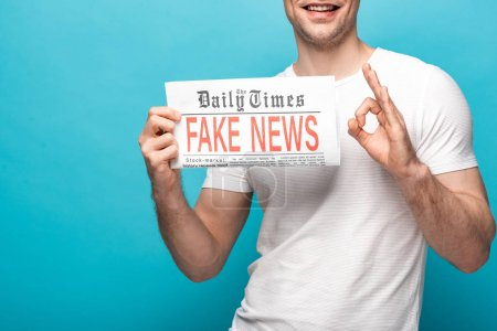 Photo for Cropped view of smiling man showing ok sign while holding newspaper with fake news on blue background - Royalty Free Image