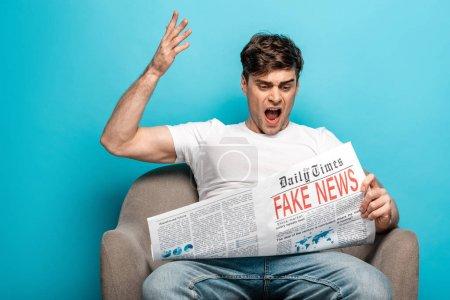 Foto de Hombre enojado gesturing mientras se sienta en el sillón y la lectura de periódico con noticias falsas sobre fondo azul - Imagen libre de derechos