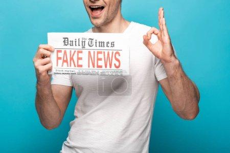 Photo pour Vue recadrée de l'homme affichant le signe ok tout en affichant le journal avec de fausses nouvelles sur le fond bleu - image libre de droit