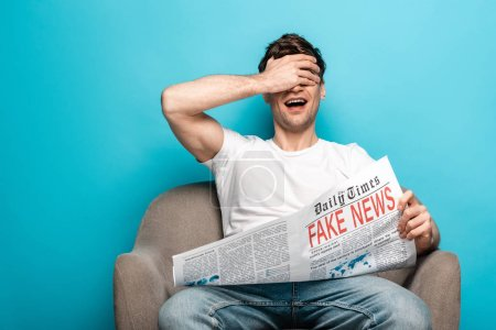Photo for Young man laughing while sitting in armchair and holding newspaper with fake news on blue background - Royalty Free Image