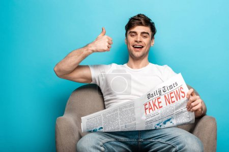 Photo for Cheerful young man showing thumb up while sitting in armchair and holding newspaper with fake news on blue background - Royalty Free Image