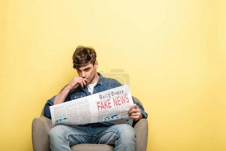 Photo pour Jeune homme attentif s'asseyant dans le fauteuil et journal de lecture avec de fausses nouvelles sur le fond jaune - image libre de droit