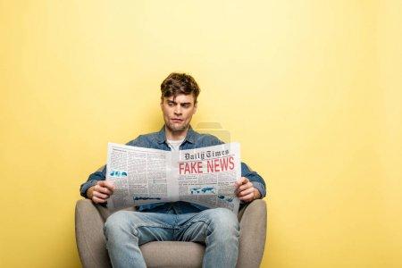Photo pour Jeune homme sérieux s'asseyant dans le fauteuil et lisant le journal avec de fausses nouvelles sur le fond jaune - image libre de droit