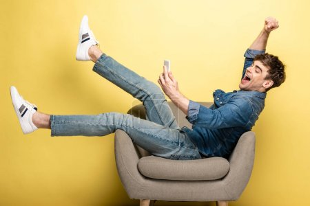 Photo for Happy man using smartphone while sitting in armchair and showing winner gesture on yellow background - Royalty Free Image