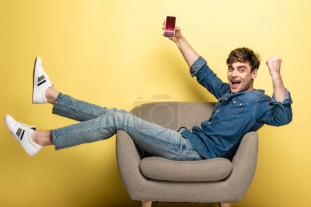 Photo for Handsome smiling man in denim clothes holding smartphone with trading courses app sitting on armchair on yellow - Royalty Free Image