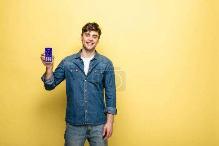 Photo for Handsome smiling man in denim clothes holding smartphone with health app on yellow - Royalty Free Image