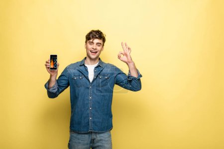 Foto de Handsome smiling man in denim clothes holding smartphone with infographic and showing ok sign, on yellow - Imagen libre de derechos