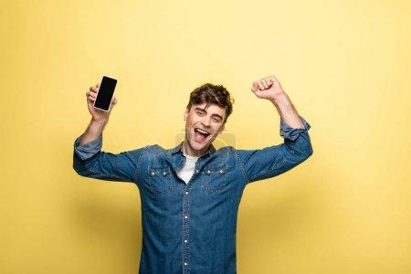Photo pour Joyeux jeune homme tenant smartphone avec écran blanc et montrant geste gagnant sur fond jaune - image libre de droit