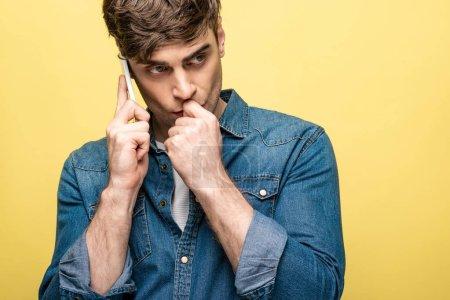 Photo pour Homme pensif regardant loin tout en parlant sur le smartphone isolé sur le jaune - image libre de droit