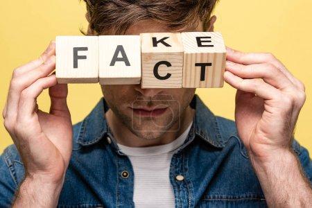 Photo pour Vue recadrée de l'homme tenant des cubes en bois avec faux lettrage fait isolé sur jaune - image libre de droit