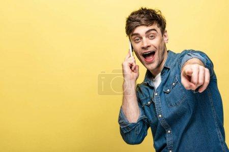 Photo pour Joyeux jeune homme pointant du doigt la caméra tout en parlant sur smartphone sur fond jaune - image libre de droit