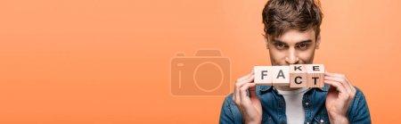 Photo pour Plan panoramique de l'homme positif montrant des cubes en bois avec de faux lettrage fack isolé sur jaune - image libre de droit
