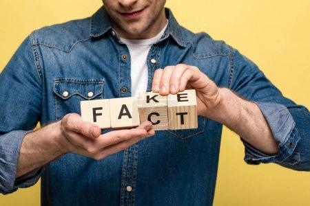 Photo pour Vue recadrée d'un homme souriant tenant des cubes en bois avec un faux lettrage isolé sur jaune - image libre de droit