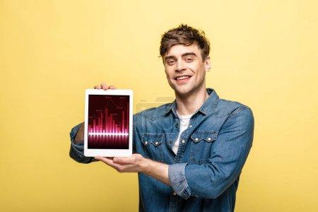 Photo pour Homme de sourire beau dans des vêtements de denim affichant la tablette numérique avec le graphique, d'isolement sur le jaune - image libre de droit