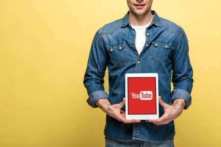 Foto de KYIV, UKRAINE - MAY 16, 2019: cropped view of man in jeans clothes showing digital tablet with youtube app, isolated on yellow - Imagen libre de derechos