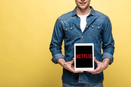 Foto de Kiev, Ucrania - 16 de mayo de 2019: vista recortada del hombre en ropa de jeans que muestra la tableta digital con aplicación netflix, aislado en amarillo - Imagen libre de derechos