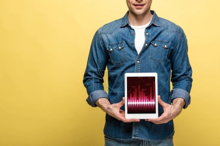 Foto de Cropped view of man in denim clothes holding digital tablet with graph, isolated on yellow - Imagen libre de derechos