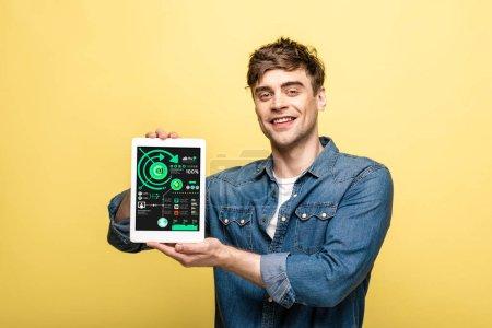 Photo pour Bel homme souriant en denim montrant tablette numérique avec application infographique, isolé sur jaune - image libre de droit
