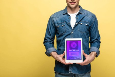 Photo for Cropped view of man in denim clothes holding digital tablet with shopping app, isolated on yellow - Royalty Free Image