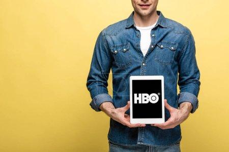 Photo pour Kiev, Ukraine - 16 mai 2019: vue recadrée de l'homme en jeans montrant une tablette numérique avec l'application Hbo, isolée sur le jaune - image libre de droit
