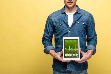 Foto de Vista recortada del hombre en ropa de mezclilla sosteniendo tableta digital con aplicación de salud, aislado en amarillo - Imagen libre de derechos