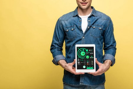 Photo for Cropped view of man in denim clothes holding digital tablet with infographic, isolated on yellow - Royalty Free Image
