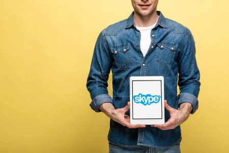 Photo for KYIV, UKRAINE - MAY 16, 2019: cropped view of man in jeans clothes showing digital tablet with skype app, isolated on yellow - Royalty Free Image