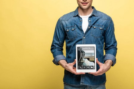 Photo pour Vue recadrée de l'homme en denim tenant tablette numérique avec l'application billets, isolé sur jaune - image libre de droit