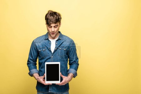 handsome man holding digital tablet with blank screen on yellow background