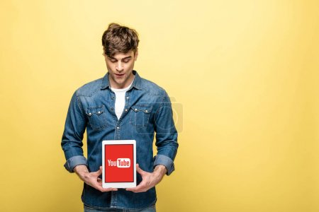 Photo for KYIV, UKRAINE - MAY 16, 2019: handsome man in jeans clothes looking at digital tablet with youtube app, isolated on yellow - Royalty Free Image