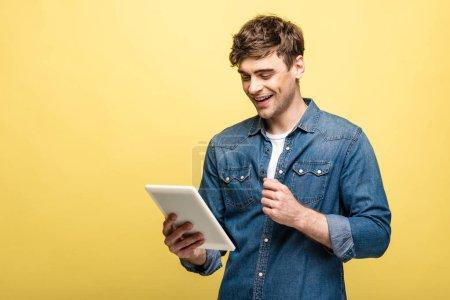 joven alegre en camisa de mezclilla usando tableta digital sobre fondo amarillo