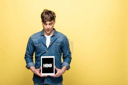 Photo for KYIV, UKRAINE - MAY 16, 2019: handsome man in jeans clothes looking at digital tablet with HBO app, isolated on yellow - Royalty Free Image