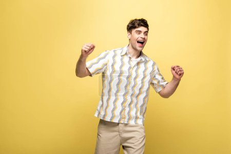 Photo for Cheerful young man showing winner gesture while looking away on yellow background - Royalty Free Image