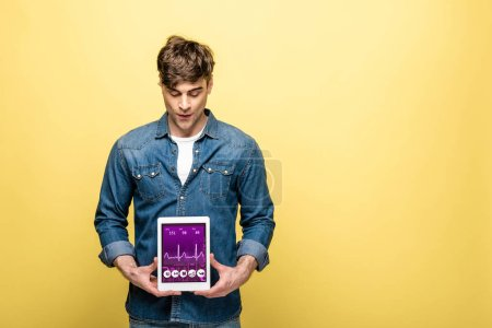 Photo for Handsome man in denim clothes looking at digital tablet with health app, isolated on yellow - Royalty Free Image