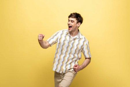 Photo pour Jeune homme heureux dansant et souriant sur le fond jaune - image libre de droit