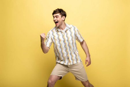 Photo for Cheerful young man looking away and showing winner gesture on yellow background - Royalty Free Image