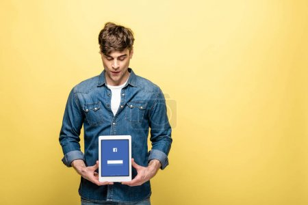 Photo for KYIV, UKRAINE - MAY 16, 2019: handsome man in jeans clothes looking at digital tablet with facebook app, isolated on yellow - Royalty Free Image