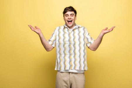 Foto de Joven alegre mostrando gesto de encogimiento de hombros y sonriendo a la cámara sobre fondo amarillo - Imagen libre de derechos